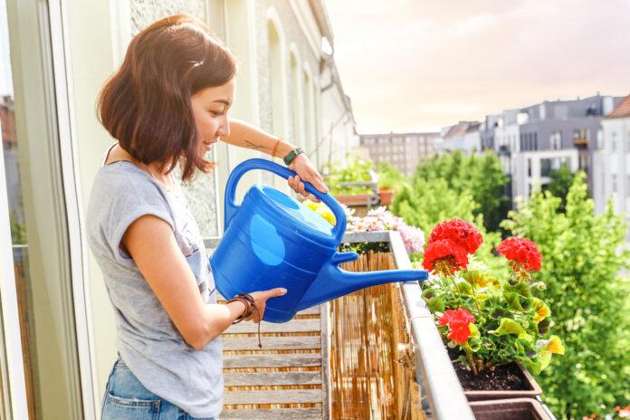 Eine Frau gießt Blumen auf ihrem Balkon.